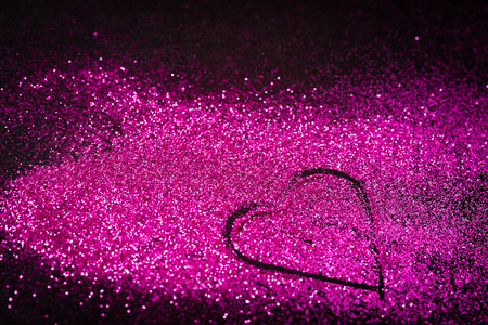 heart background: Pink glitter shaped as a heart on black background. Copy space.