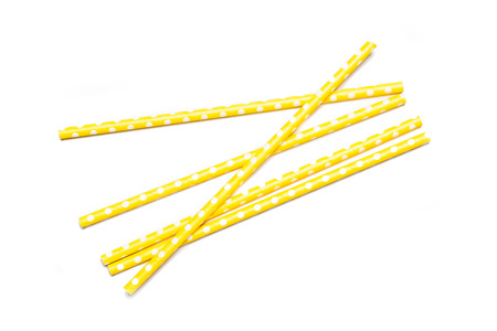 tubules: Several yellow drinking straws in retro style with yellow and white stripes on white background Stock Photo
