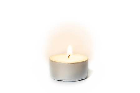 Shining flame on a tea light candle on white background