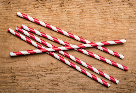 tubules: Several red drinking straws in retro style with red and white stripes on wood background Stock Photo