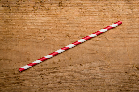tubules: A single red drinking straw in retro style with red and white stripes on wood background Stock Photo