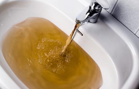 흰색 싱크대에 실행 더러운 갈색 물. 매우 건강에 해로운 보인다