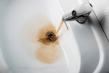 cocina antigua: brown agua sucia cayendo en un fregadero blanco. Se ve muy poco saludable, Foto de archivo
