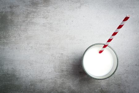 vaso de leche: Vaso de leche y una pajita de color rojo y blanco sobre una mesa de hormigón. Vista desde la anterior. Foto de archivo