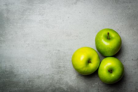 manzana verde: Tres manzanas verdes en el fondo de hormigón