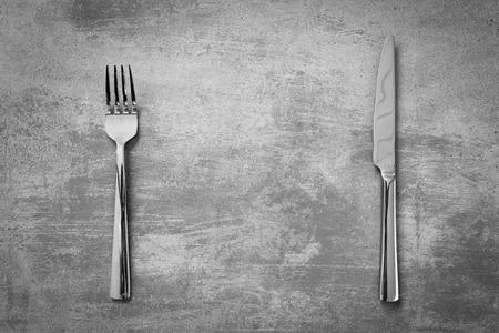 Tenedor y un cuchillo en el grunge de fondo de hormigón