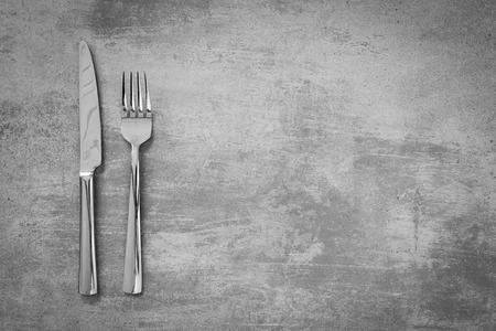 grunge silverware: Fork and knife on grunge concrete background Stock Photo