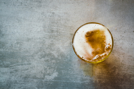 top angle view: Glass of beer on a concrete table
