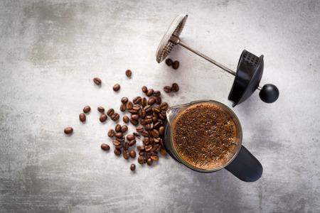 Fabricante de café francés de prensa con granos de café en la mesa de concreto Foto de archivo - 56077699