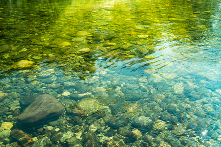 Rippling water with sunbeams and stones in the water