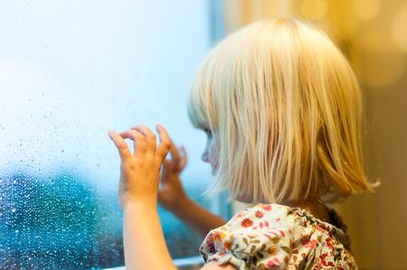 condensacion: Niña mirando por la ventana. Está lloviendo y ella está esperando.