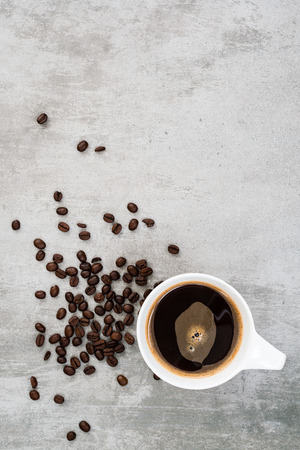black bean: Cup of coffee and coffee beans on concrete background with top view Stock Photo