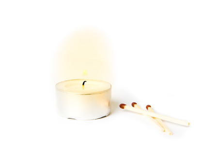 tea candle: Lit tea candle with matches on white background