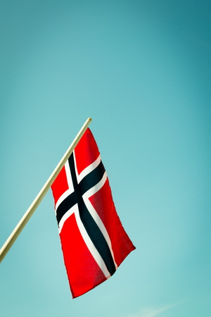 vintage wave: Norwegian flag waving with the sky as the background
