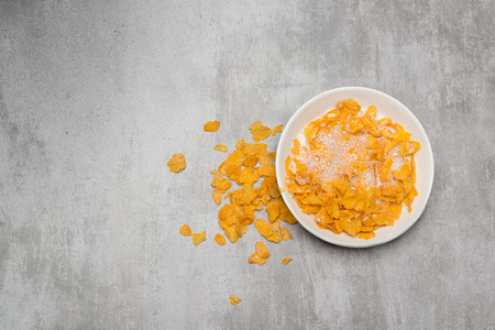 corn meal: Cornflakes cereal with milk in a bowl on a concrete table Stock Photo