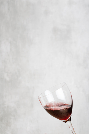 glass of red wine: Glass of red wine in front of a concrete background