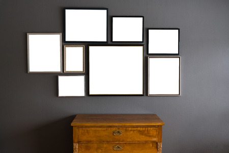 frame wall: Blank frames in different sizes on a gray wall with a wood dresser in the front