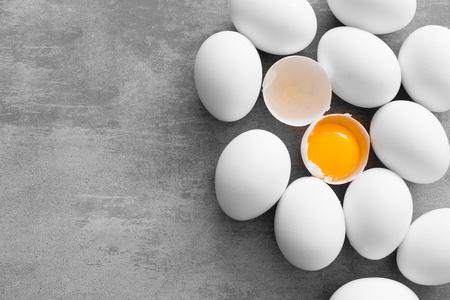 huevo blanco: Huevos blancos en una mesa concreta. Un huevo se agrieta y se puede ver la yema amarilla Foto de archivo