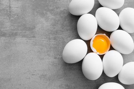 Huevos blancos en una mesa concreta. Un huevo se agrieta y se puede ver la yema amarilla Foto de archivo - 74859994