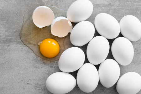 huevo blanco: White eggs on a concrete table. One egg is broken and the yolk is on the table