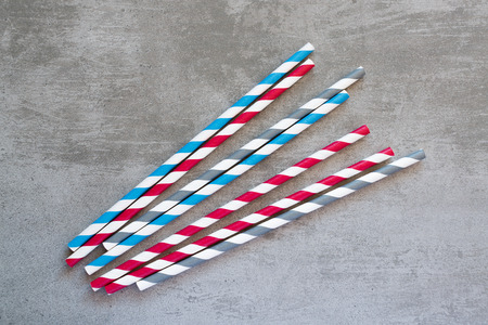Red, blue, gray and white striped drinking straws on concrete background
