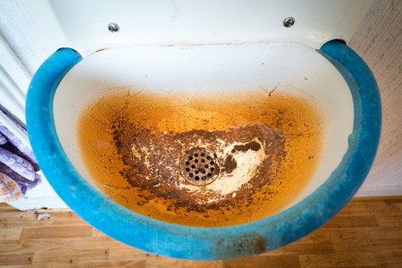Old dirty white and blue sink with brown stain Stock Photo