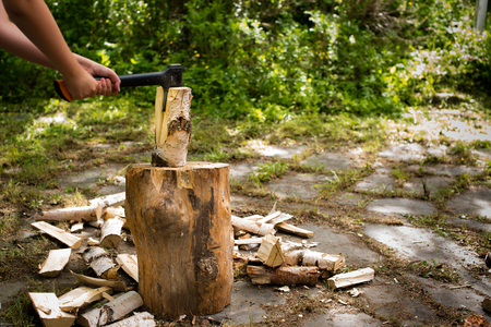 young man chopping wood with an axe outside on a chopping block Stock Photo - 81558328