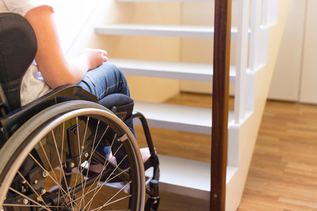Young person in a wheelchair in front of a stair Stock Photo