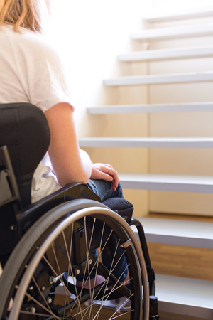 Young person in a wheelchair in front of a stair