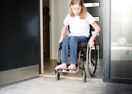 Young person in a wheelchair moving over a low doorstep Stockfoto