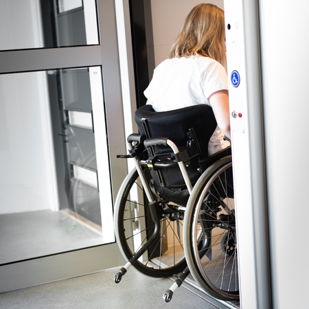 Young person in a wheelchair entering an elevator