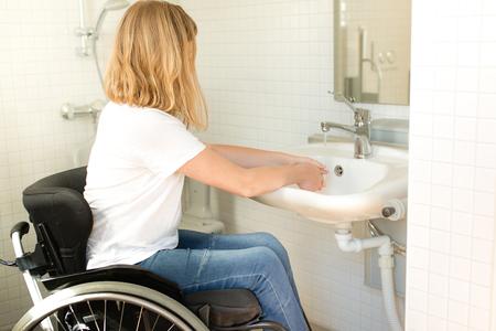 Jonge persoon in een rolstoel wassen handen Stockfoto