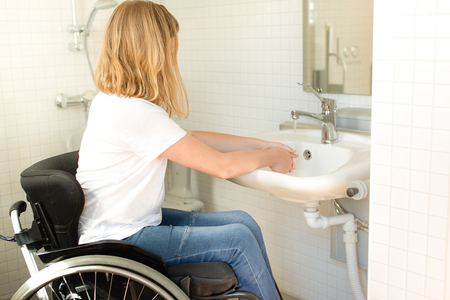 Young person in a wheelchair washing hands Foto de archivo