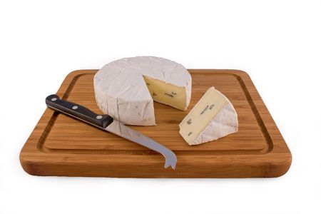 A slice of Cambozola cheese on a wooden board with a knife for soft cheese