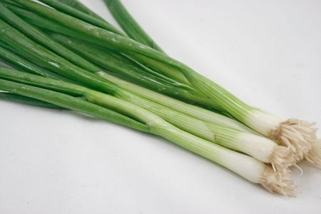 A bunch of green onions on a white background
