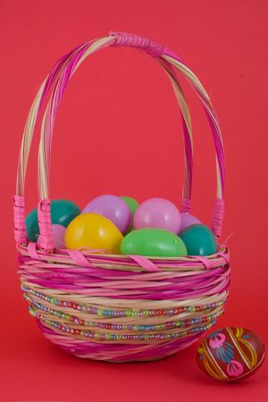 A basket full of plastic eggs (to be filled with candy) and pisanka egg on a side photo