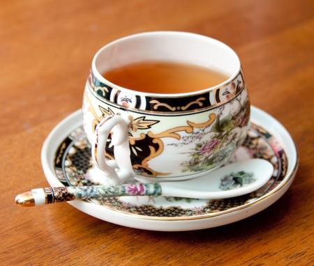 Zwarte thee in een sierlijke porseleinen beker Stockfoto