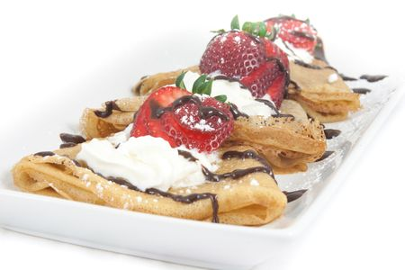 Crepes with strawberries, whipped cream, chocolate and icing sugar