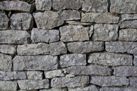 Gray wall of old uneven stones, horizontal Stock Photo