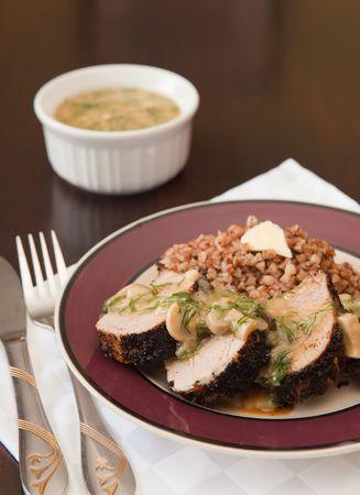 Geroosterd varkensvlees in kruiden met champignonsaus en boekweit Stockfoto