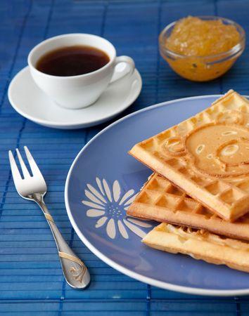 Drie warme Belgische wafels met gem en koffie