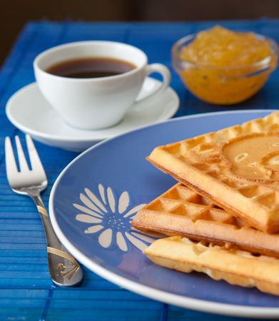 Three hot belgian waffles with gem and coffee