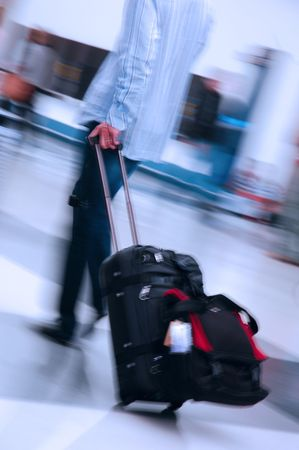 lug: Man pulling suitcase through a busy airport
