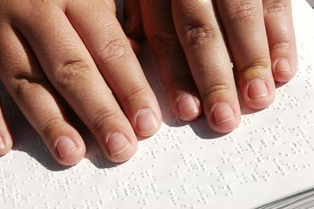 Blind person reading Bible written in Braille Stock Photo