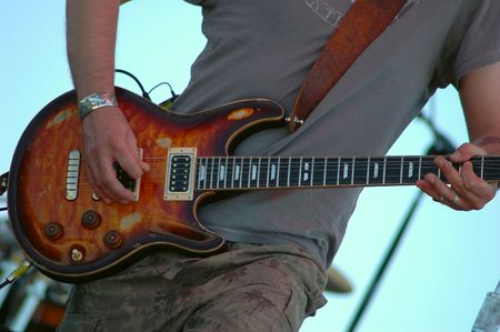 Close-up of an electric guitar played by a musician