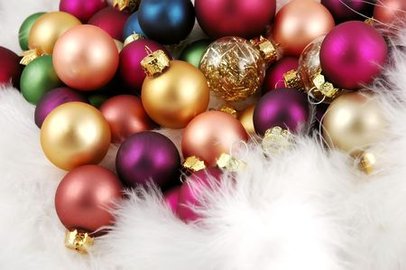 Pile of Christmas ornaments nestled in a bed of white feathers