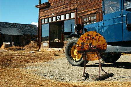 Abandoned gas station with truck and sign at the ghost town of Bodie, California photo