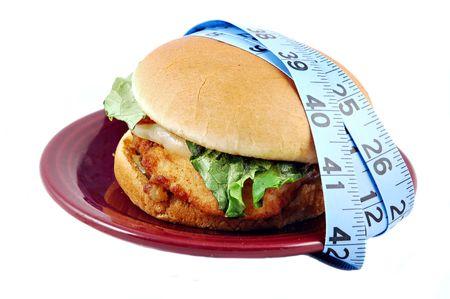 sandwich au poulet: Sandwich au poulet frit avec laitue, tomates, provolone et sur un petit pain sur une plaque entour� d'un ruban � mesurer.