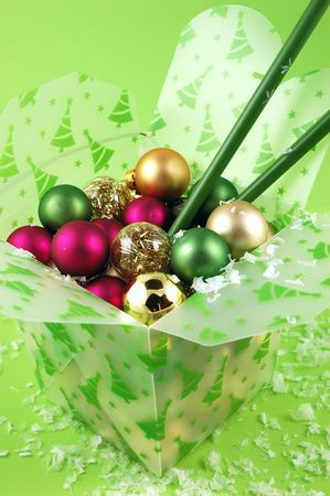 Christmas ornaments in a take-out food container with chopsticks on a lime green background Stock Photo