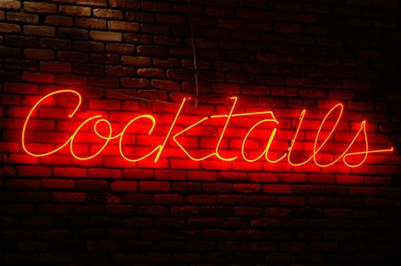 Cocktails neon sign illuminated against a brick wall at night Stok Fotoğraf